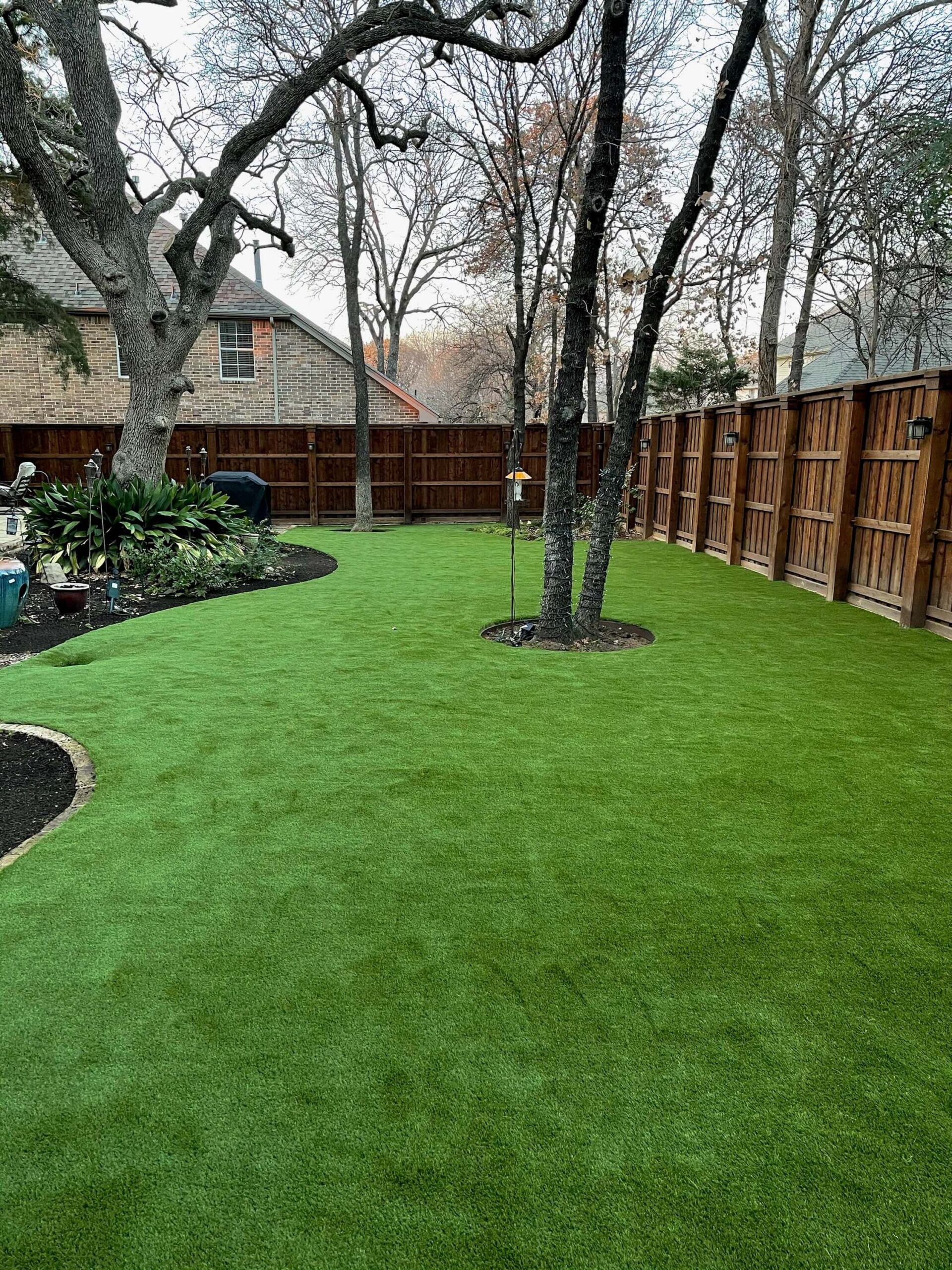 backyard with artificial lawn installation