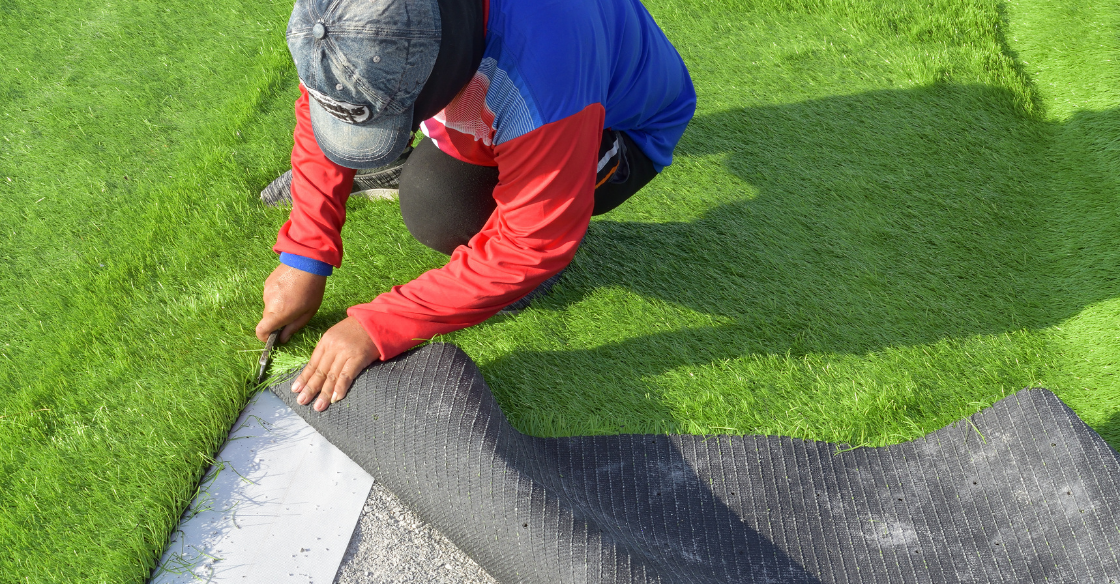 A professional artificial turf installer lays down the artificial turf.