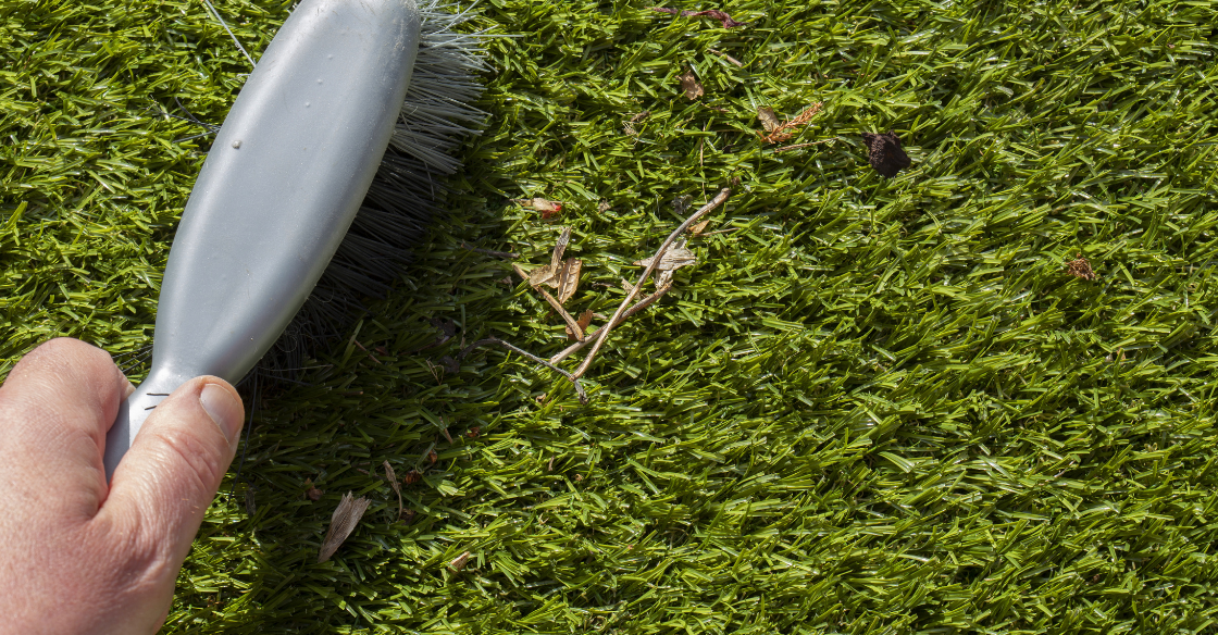A man using a brush with synthetic bristles to clean his artificial grass.